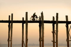 Cyclist is driving over U Bein's Bridge Royalty Free Stock Photography