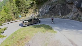 Cyclist driving through sharp turn on a slope stock video footage
