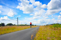 A cyclist on an empty rural road Royalty Free Stock Image