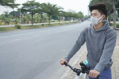 Unhappy with smog. Cyclist in face mask due to smog in the city Stock Photo