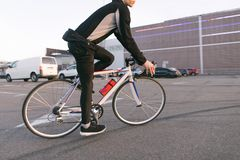 Cyclist on a fast-paced bike ride, ride in the parking lot, on the background of the mall. Close-up photo of a cyclist on a fast-paced bike ride, ride in the royalty free stock photos