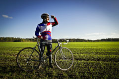 Cyclist in the field next to the bicycle Stock Image