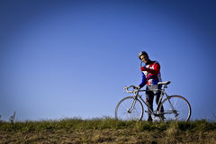 Cyclist in the field next to the bicycle Stock Photography