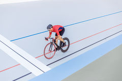 Cyclist finishes on velodrome. Professional athlete in a red T-shirt and a black bicycle Stock Image