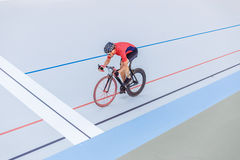 Cyclist finishes on velodrome. Professional athlete in a red T-shirt and a black bicycle Stock Photography