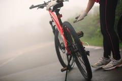 Cyclist fix the bike chain on road. Cyclist fix the bike chain on foggy road Stock Photo