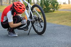 Cyclist fix the problem of mountain bike in park. Female cyclist fix the problem of mountain bike in park Stock Photos