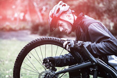 Cyclist fixing bike Royalty Free Stock Image