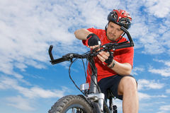 Cyclist fixing his mountain bike his mountain bike Royalty Free Stock Photography