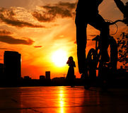 Cyclist in the foreground against a bright red sunset above city and silhouette of girl Royalty Free Stock Photos