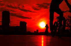 Cyclist in the foreground against a bright red sunset above city and silhouette of girl Stock Photos