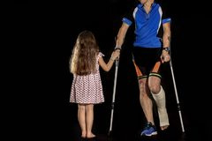 Cyclist with fracture of heel. A little girl and men with crutches and plaster cast Stock Image