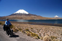 Cyclist in front of Parinacota volcano. Woman cyclist standing in front of volcano Parinacota in Parc National Lauca on the border between Chile and Argentina Royalty Free Stock Photo