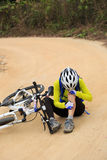 Cyclist getting injured while falling from mountain bike. Female cyclist getting injured while falling from mountain bike on forest trail Stock Images