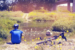 Cyclist getting some rest at the riverside with a  Stock Images