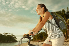 Cyclist girl with backpack enjoying view of beautiful  island Stock Images