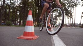 Cyclist go round traffic cones. Young handsome man riding a vintage bicycle. Sporty guy cycling at the park. Healthy royalty free stock photography