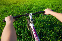 Cyclist in a green field on a bike. travel Royalty Free Stock Photos