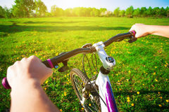 Cyclist in a green field on a bike. travel Royalty Free Stock Image