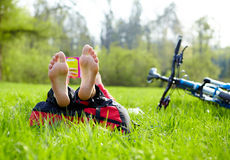 Cyclist on a halt reads lying in fresh green grass barefoot Stock Photo