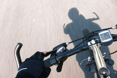 Cyclist Hand Glove on Speeding Bicycle Handlebar royalty free stock photo