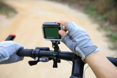 Cyclist hands set the action camera. Mounted on mountain bike Royalty Free Stock Photography