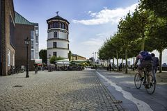 A cyclist heading towards the Maritime Museum tower along the river Rhine along the cycle path in Dusseldorf, Germany. A cyclist heading towards the Maritime royalty free stock image