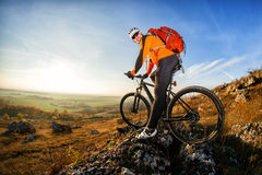 Cyclist in helmet and glasses on mountain bike stands on the precipice of hill under blue sky and sun. Wide angle view Royalty Free Stock Image