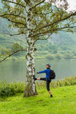 The cyclist in the helmet near the tree. Germany. Moselle. An athlete doing exercises near the birch. A man in a blue t-shirt, hat and jodhpurs. In the Royalty Free Stock Photos