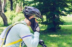 A cyclist in a helmet is riding in the park and talking on the phone stock image