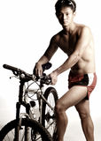 Cyclist and his mountain bike. Muscular cyclist and his mountain bike Royalty Free Stock Image