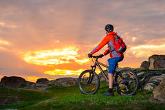 Cyclist with his Mountain Bike Looking at the Beautiful Sunset on Spring Rocky Trail. Extreme Sports and Adventure Concept. Royalty Free Stock Photography