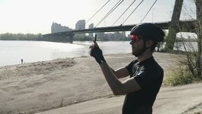 Cyclist holding camera phone taking pictures of river and city standing on the hill. Bridge and sun shines in background. Slow mot stock footage