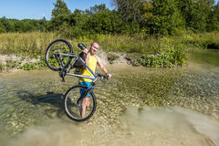 Cyclist holding his bicycle, standing in a river Royalty Free Stock Image