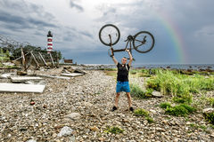 The cyclist holds his bike on a rainbow background and Shepelevs. Shepelevsky Cape.Russia.26 Jun 2016.The cyclist holds his bike on a rainbow background and Royalty Free Stock Images