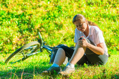 Cyclist holds a his bruised knee. While sitting on the lawn Stock Image