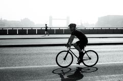Cyclist and jogger on London Bridge, London, UK royalty free stock photo