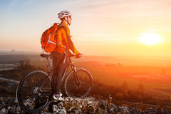 Cyclist leaning against bicycle in front of scenic skyline view of sunset. Royalty Free Stock Photo