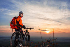 Cyclist leaning against bicycle in front of scenic skyline view of sunset. Stock Photo