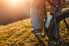Cyclist legs riding mountain bike on the hill in spring time. Close-up. Detail of the cycle. Whell and bottle. Legs and shoes. Field, grass and sun. Travel in Stock Photos