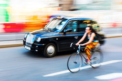 Cyclist and London Taxi in motion blur in the city traffic of London, UK Royalty Free Stock Photos