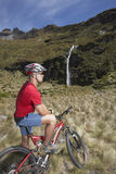 Cyclist Looking At Waterfall In Field Royalty Free Stock Images