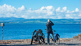 Cyclist looks out over Beauly Firth. Cyclist looks out to hills beyond the Beauly Firth from Clachnaharry sea lock on 1st October 2016 stock photos