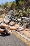 Cyclist lying on the road after an accident Royalty Free Stock Photos