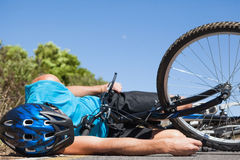 Cyclist lying on the road after an accident Stock Images