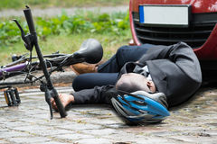 Cyclist Lying On Street After Accident. Young African Male Cyclist Lying On Street After Accident Royalty Free Stock Photos