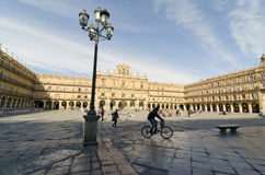 Cyclist in Main Square. SALAMANCA, SPAIN - FEBRUARY 5, 2013: Cyclist and pedestrian. The Plaza Mayor of Salamanca, Spain, is an urban square built as Castilian Stock Image