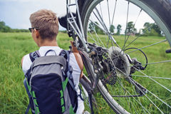 Cyclist man carries bike in field Stock Image