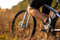 Cyclist man legs riding mountain bike on outdoor trail in autumn forest Royalty Free Stock Images