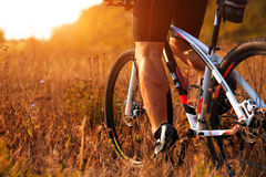 Cyclist man legs riding mountain bike on outdoor trail in autumn forest Stock Images